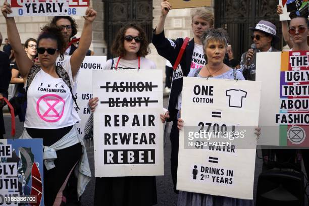 Protesters from Extinction Rebellion hold up antifashion placards as they block a road on the third day of London Fashion Week in London on September...