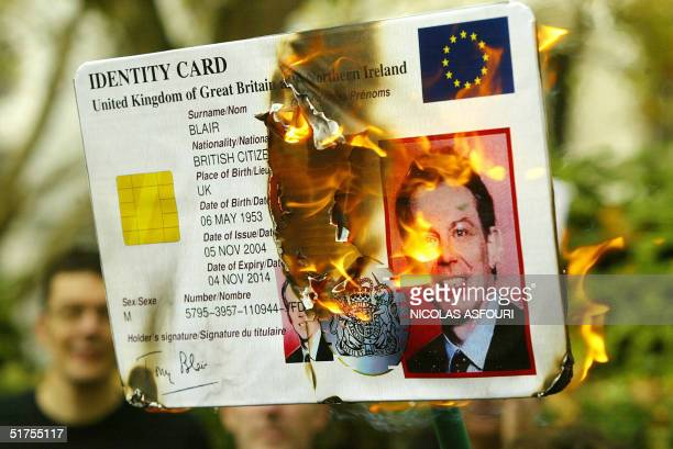 """Protesters from """"NO2ID"""" burn an identity card of British Prime minister Tony Blair in London 17 November, 2004. The group was demonstrating outside..."""