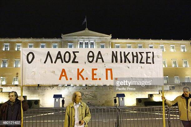 Protesters from the AKEP hold a banner that reads 'The people will win' outside the Greek Parliament. Greek protesters from SYRIZA , the main...