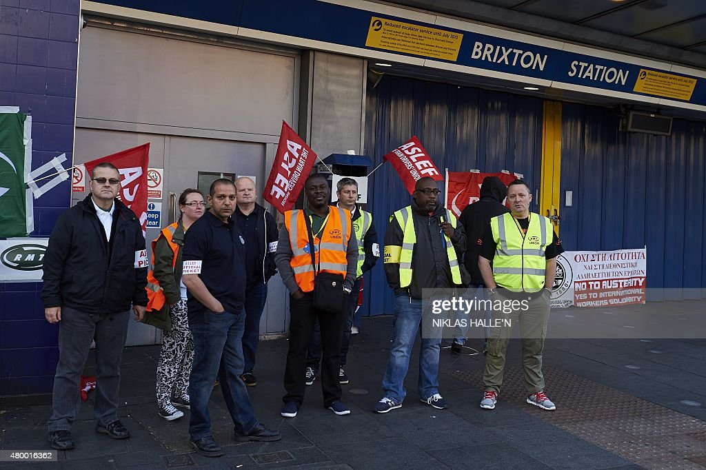 Protesters from the ASLEF and RMT unions stand at the locked gates of Brixton underground station during a tube strike in London on July 9, 2015. London's roads, buses and overland trains struggled to cope in Thursday's morning rush hour as commuters battled into work in the face of London Underground's first strike shutdown since 2002. AFP PHOTO / NIKLAS HALLE'N