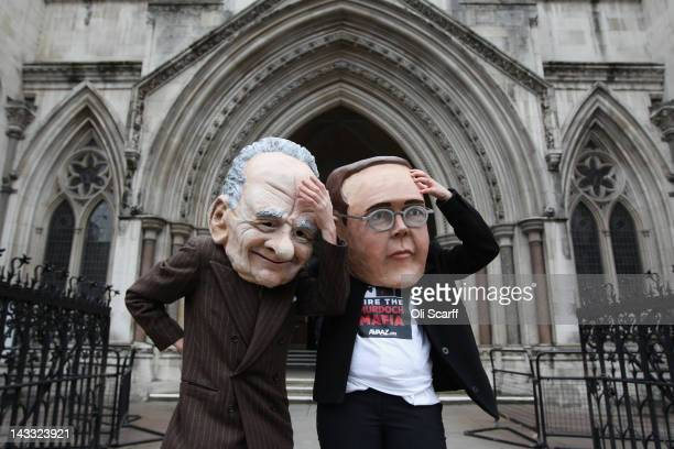 Protesters from the campaign group 'Avaaz' demonstrate outside the High Court with large James and Rupert Murdoch masks as former News International...