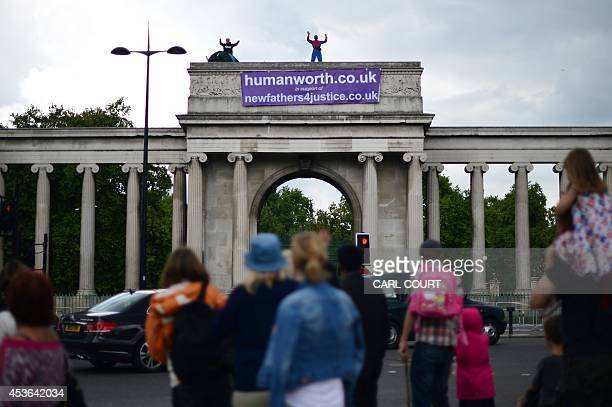 Protesters from the group formerly know as Fathers 4 Justice are pictured on top of the gate of Apsley House at Hyde Park Corner in central London on...