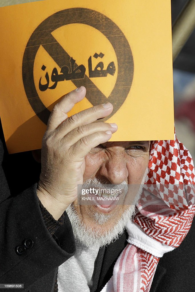 Protesters from the Islamic Action Front and other opposition parties hold signs read 'Boycotting' during a protest in Amman on January 18, 2013. Some 2,000 protesters including Islamists, youths and leftists held a sit-in the Jordanian capital, rejecting as 'cosmetic' a general election due to be staged next week.