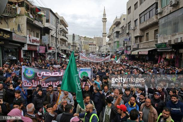"Protesters from the Islamic Action Front and others march with the Muslim Brotherhood flag and a banner reading in Arabic ""Jerusalem will remain Arab..."