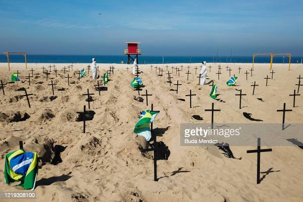Protesters from the NGO 'Rio De Paz' dig symbolic graves as a sign of protest in Copacabana beach on June 11, 2020 in Rio de Janeiro, Brazil....