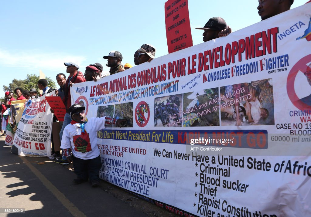 Protesters from various Southern African Development Community (SADC) countries holds a banner as they demonstrate near the entrance to Department of International Relations and Cooperation where the SADC Summit is being held on August 19, 2017 in Pretoria. The protesters are demanding for the Democratic Republic of Congo (DRC) President Joseph Kabila to step down, and also calling on South Africa to set an example in the handling of the Zimbabwe's first lady Grace Mugabe who is seeking diplomatic immunity for an alleged assault in South Africa on a a 20-year-old model. / AFP PHOTO / Phill Magakoe
