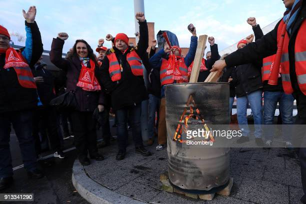 Protesters gather around a brazier barrel during a 24 hour strike called by labor union IG Metall outside the BMW Motorrad motorcycle factory...