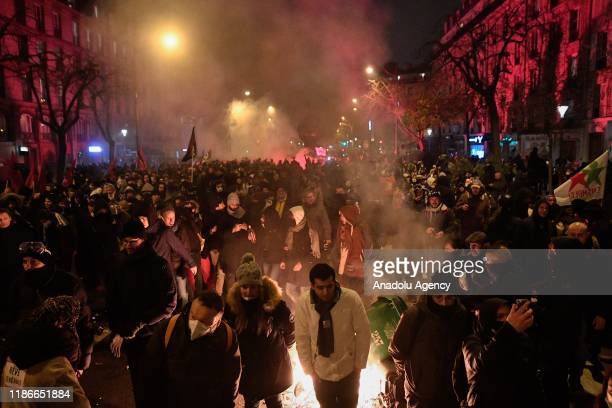 Protesters gather around a fire during a protest against President Emmanuel Macron's controversial pension plans and in support of the national...