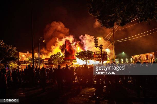 Protesters gather around a liquor store in flames near the Third Police Precinct on May 28, 2020 in Minneapolis, Minnesota, during a protest over the...