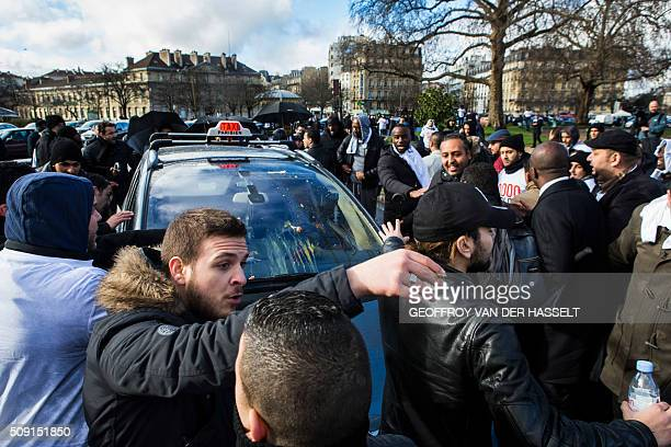 Protesters gather around a taxi that received eggs on its windshield on the Place de la Nation in Paris on February 9 during a demonstration by...