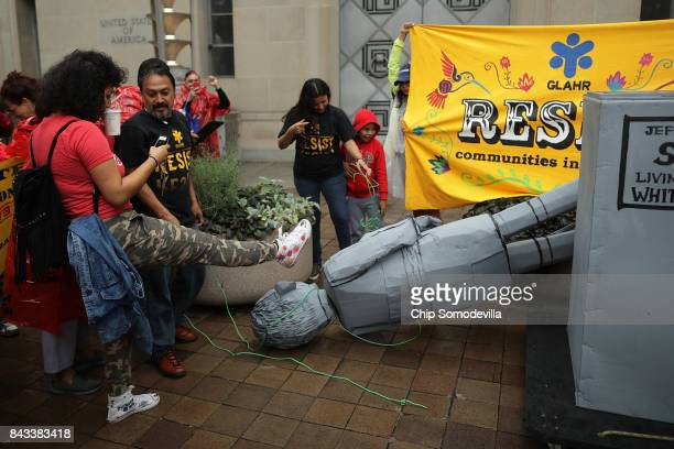 Protesters gather around a toppled mock statue of Attorney General Jeff Sessions in front of the Department of Justice to demonstrate against the...