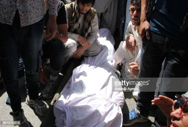 Protesters gather around the dead body of a protester after clashing with police during a protest against a suicide bomb attack in Kabul Afghanistan...