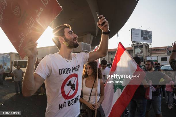 Protesters gather at an antigovernment demonstration blocking the main highway north of Beirut on October 22 2019 in Beirut Lebanon Despite Prime...