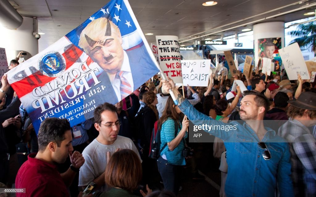 TOPSHOT - Protesters gather at the Los Angeles International airport's Tom Bradley terminal to demonstrate against President Trump's executive order effectively banning citizens from seven Muslim majority countries US President Trump signed the controversial executive order that halted refugees and residents from predominantly Muslim countries from entering the United States. / AFP / Konrad Fiedler