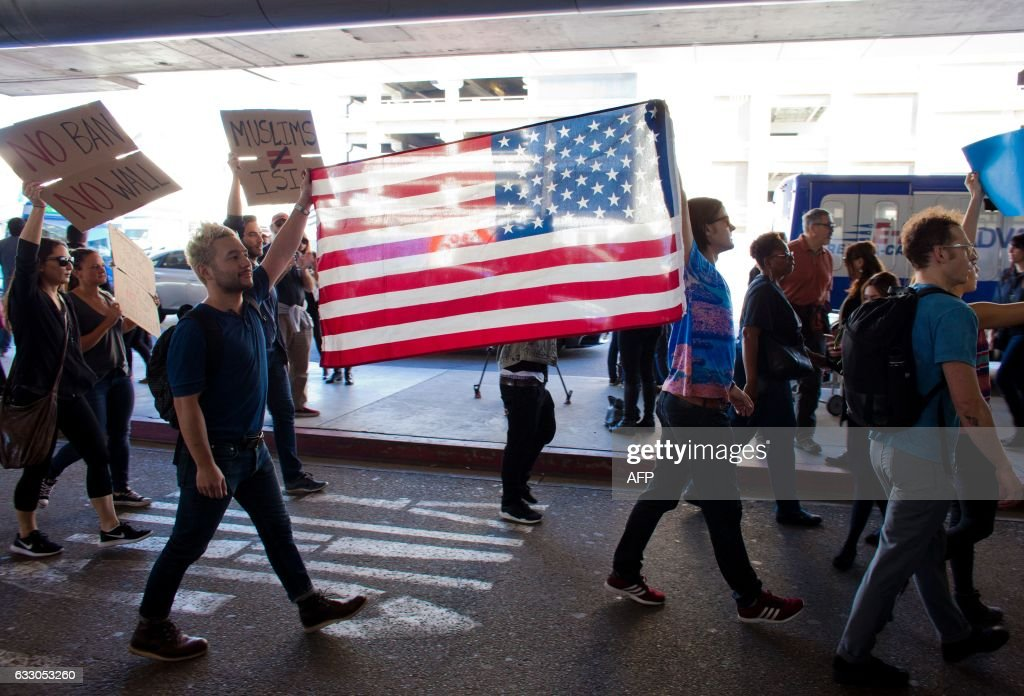 TOPSHOT - Protesters gather at the Los Angeles International airport's Tom Bradley terminal to demonstrate against President Trump's executive order effectively banning citizens from seven Muslim majority countries. US President Trump signed the controversial executive order that halted refugees and residents from predominantly Muslim countries from entering the United States. / AFP / Konrad Fiedler