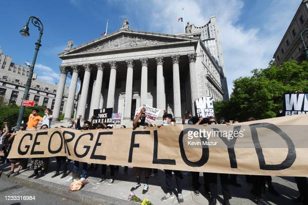 protesters gather behind a banner spelling the name of George Floyd a black man who died after a white policeman kneeled on his neck for several...