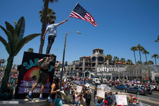 protesters gather in a demonstration on May 01 2020 in Huntington Beach California The demonstration started after the city announced it would pursue...