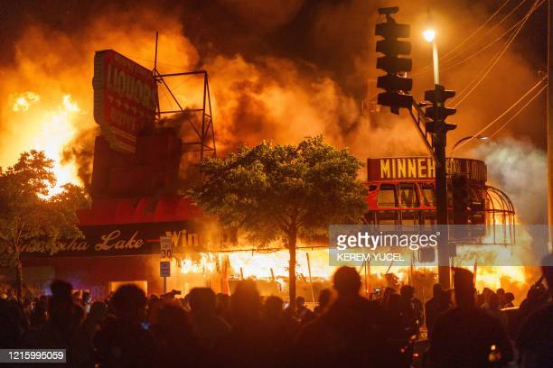 TOPSHOT Protesters gather in front of a liquor store in flames near the Third Police Precinct on May 28 2020 in Minneapolis Minnesota during a...