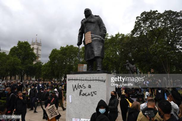 """Protesters gather in Parliament Square Garden around the statue of Winston Churchill which has graffiti with the words """"was a racist"""" outside the..."""