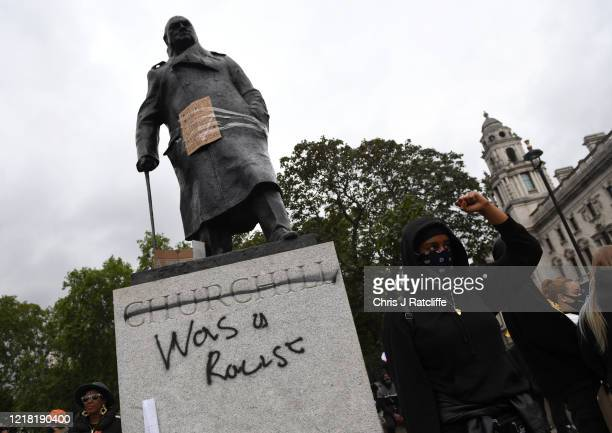 Protesters gather in Parliament Square Garden around the statue of Winston Churchill which has graffiti with the words was a racist outside the...