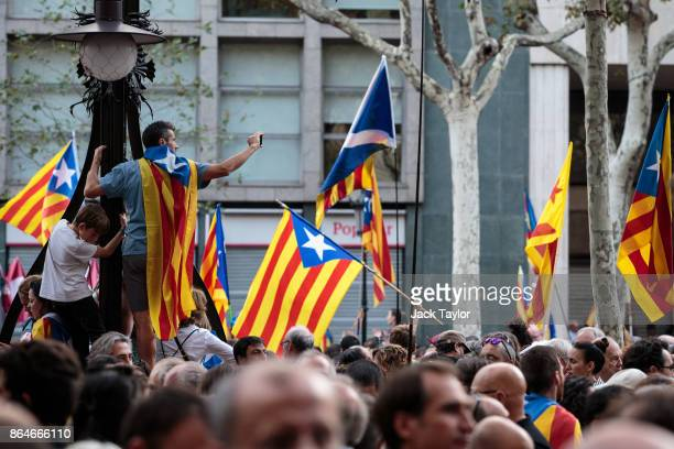 Protesters gather in the city center to demonstrate against the Spanish federal government's move to suspend Catalonian autonomy on October 21, 2017...