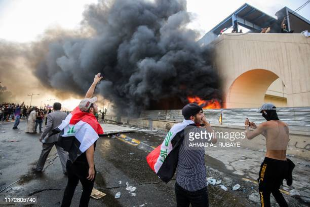 Protesters gather next to a burning building amdist clashes with Iraqi riot police during a demonstration against state corruption and poor services...