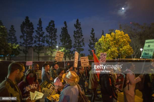 Protesters gather outside a fence erected to keep them away from the site of a speaking appearance by Conservative provocateur Milo Yiannopoulos...
