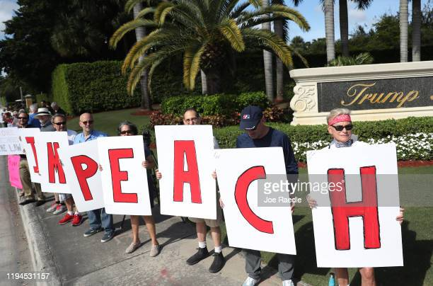 Protesters gather outside of the Trump National Doral golf resort urging congress to impeach President Donald Trump on December 17 2019 in Doral...
