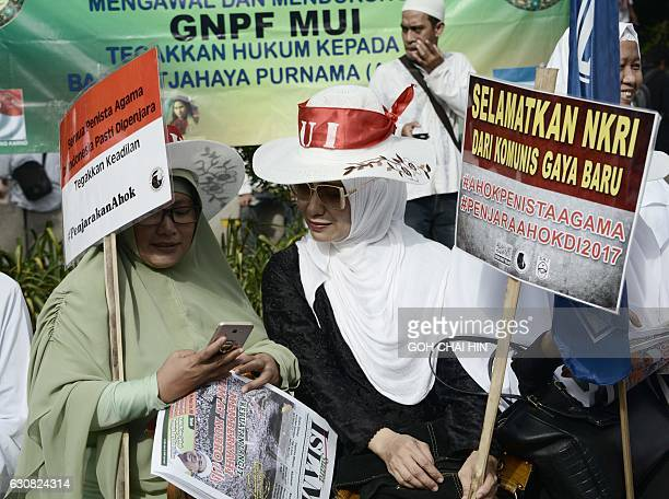 Protesters gather outside the court during the ongoing trial of Jakarta's Christian governor Basuki Tjahaja Purnama better known by his nickname Ahok...