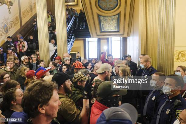 Protesters gather outside the doors of the chamber room at the Michigan Capitol Building in Lansing Michigan US on Thursday April 30 2020 Protesters...