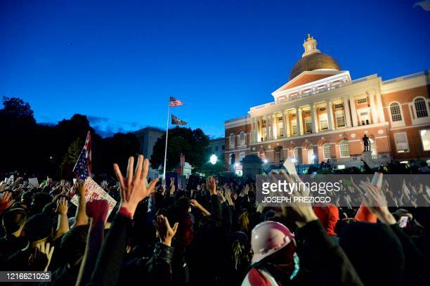 Protesters gather outside the Massachusetts State House during a demonstration over the death of George Floyd an unarmed black man who died in...