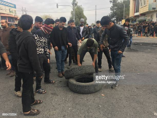 Protesters gather tires to set them on fire during the antigovernment protests in Sulaymaniyah in Sulaymaniyah Iraq on December 19 2017