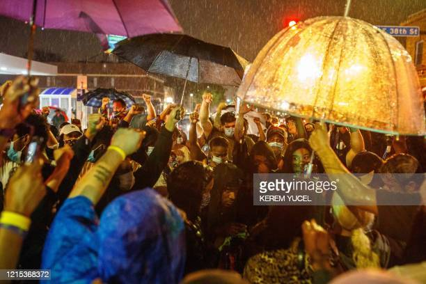 TOPSHOT Protesters gather under the rain near the spot where George Floyd died while in custody of the Minneapolis Police on May 26 2020 in...
