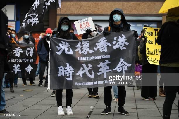 Protesters gather with banners at an event organised by Justitia Hong Kong to mourn the loss of Hong Kong's political freedoms, in Leicester Square,...