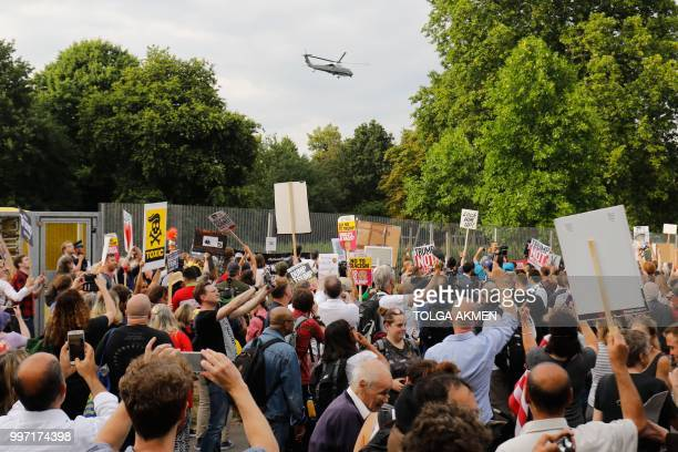 Protesters gathered at the security fence watch as US President Donald Trump and US First Lady Melania Trump leave in Marine One from the US...