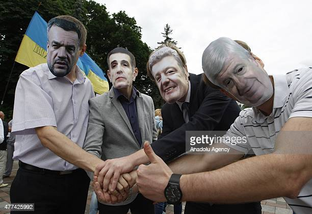 Protesters gathered in front of the Ukrainian parliament building wear the masks of Ukrainian President Petro Poroshenko and general prosecutor...