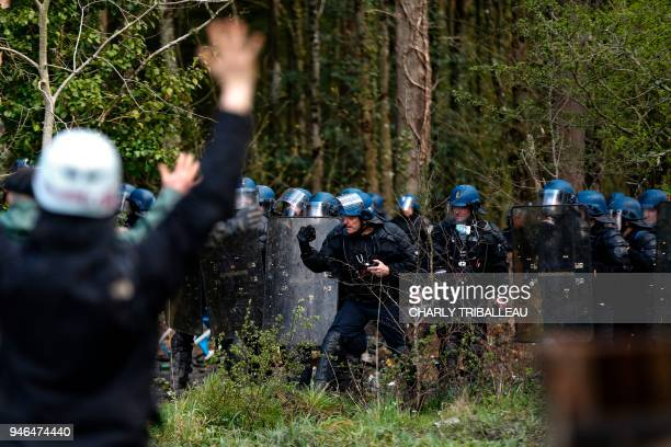 Protesters gesture as they face anti-riot officers of the Gendarmerie Mobile security forces, advancing in line during an ongoing operation to clear...