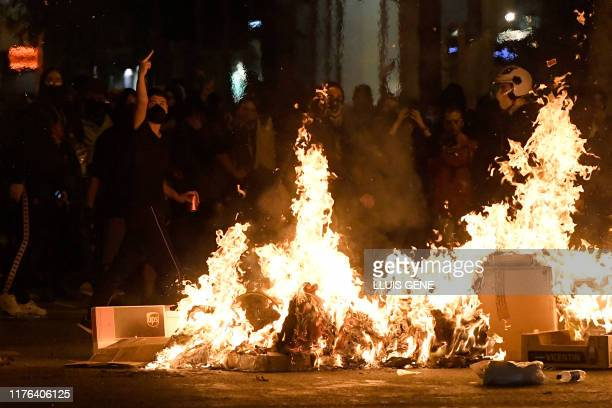 Protesters gesture behind barricades in flames after a demonstration called by the local Republic Defence Committees in Barcelona on October 17,...