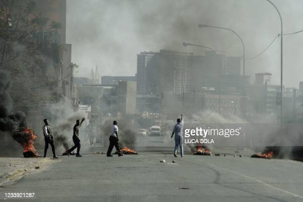 Protesters gesture towards police officers as they burn tires in Jeppestown, Johannesburg, on July 11, 2021. - Several shops are damaged and cars...