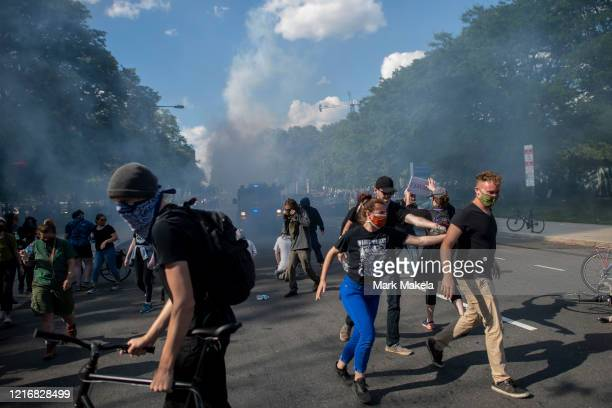 protesters guide each other away from tear gas shot by the police after a march through Center City on June 1 2020 in Philadelphia Pennsylvania...