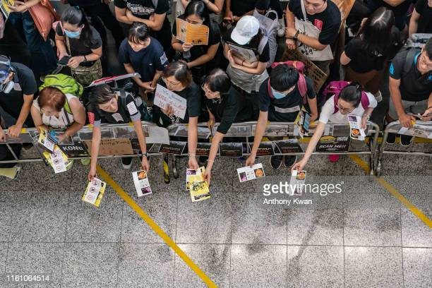 Protesters hand out leaflets at the arrival hall of the Hong Kong International Airport during a demonstration on August 11 2019 in Hong Kong China...