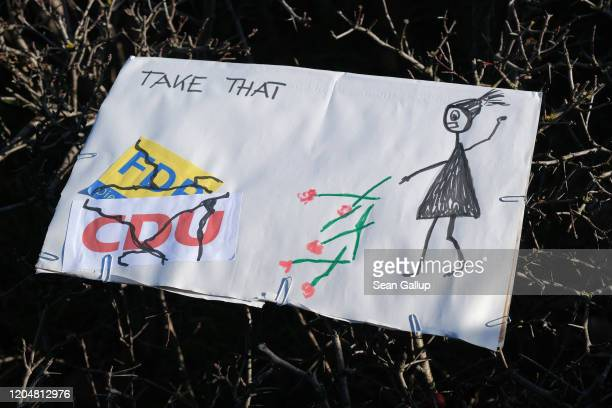 A protester's handdrawn sign refers to the tossing of congratulatory flowers on the floor by Susanne HennigWellsow leader of the Thuringia state...