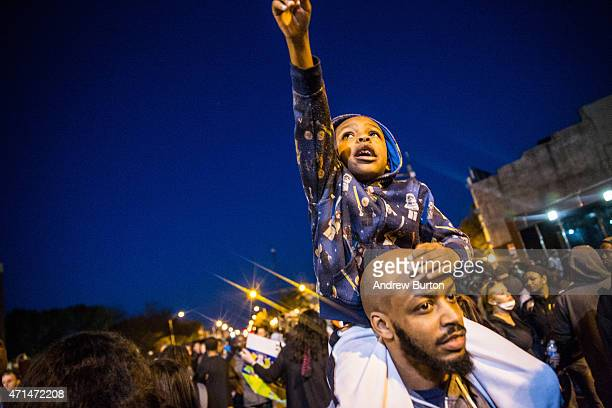Protesters hang out front of riot police minutes before a mandatory, city-wide curfew of 10 p.m. Near the CVS pharmacy that was set on fire yesterday...
