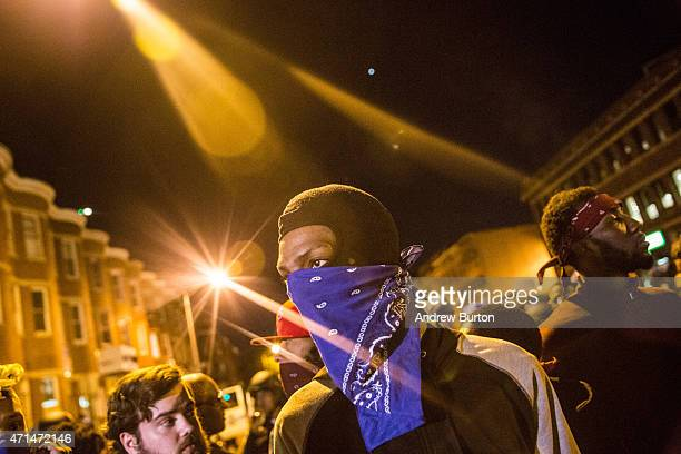 Protesters hang out near riot police minutes before a mandatory, city-wide curfew of 10 p.m. Near the CVS pharmacy that was set on fire yesterday...