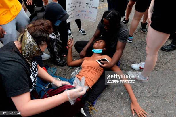 Protesters help an injured woman after clashing with police officers outside the District Four Police station during a Black Lives Matter protest...
