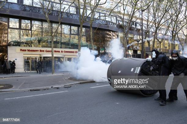 Protesters hide behind a dislodged glass recycling bin as they clash with CRS antiriot police at a demonstration on April 19 in Paris as part of a...