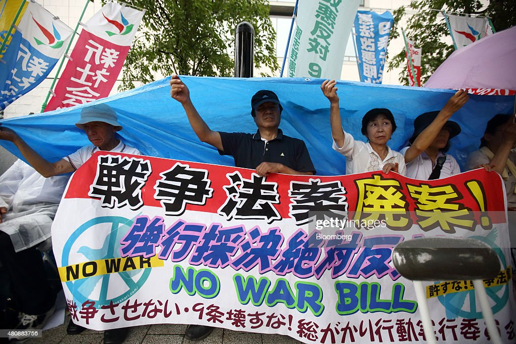 Protesters hold a banner and a tarp over their heads during a rally against the security bills outside the National Diet building in Tokyo, Japan, on Thursday, July 16, 2015. Japanese Prime Minister Shinzo Abe's security bills passed parliament's lower house Thursday after a night of noisy protests, as his push to expand the role of the military risks further eroding his public support. Photographer: Tomohiro Ohsumi/Bloomberg via Getty Images