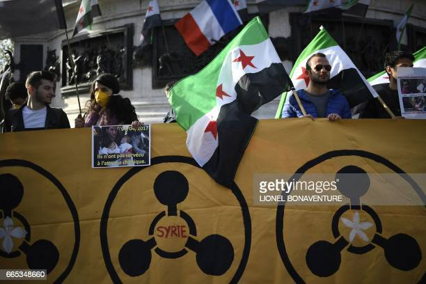 Protesters hold a banner and Syria's former independence flags during a demonstration to protest against chemical attacks in Syria on April 6 2017 on...
