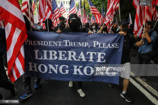 Protesters hold a banner and wave US national flags as they march from Chater Garden to the US consulate in Hong Kong on September 8 to call on the...