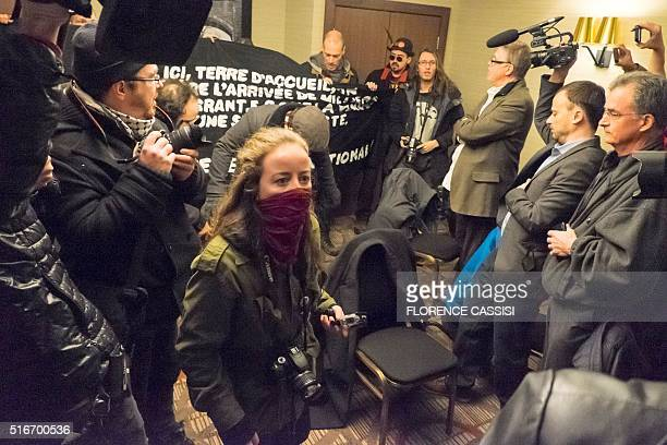Protesters hold a banner as French far right Front National president Marine Le Pen speaks at a press conferencein Quebec City on March 20 2016 Le...